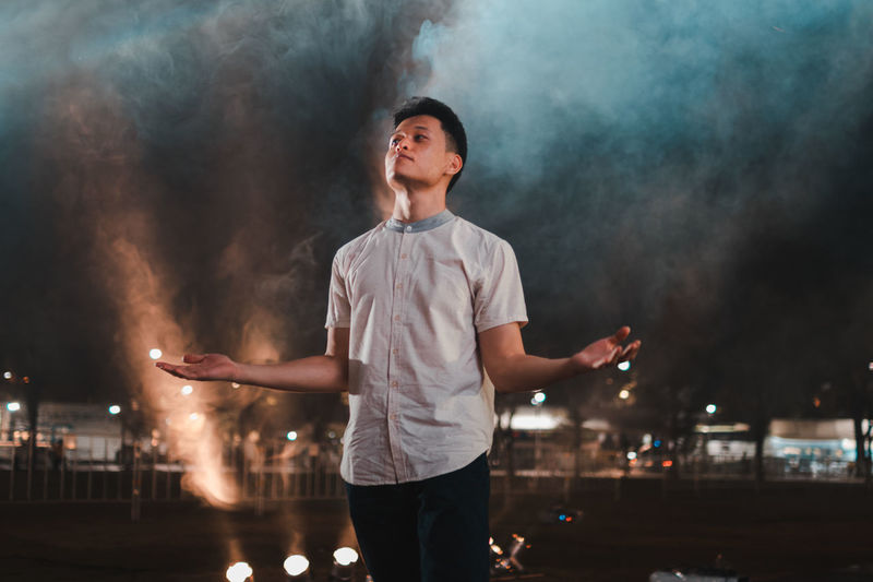 A man among smoke Smoke - Physical Structure One Person Standing Young Men Real People Smoke Power In Nature Superhero Polution Casual Clothing Superpower Smell Refreshment