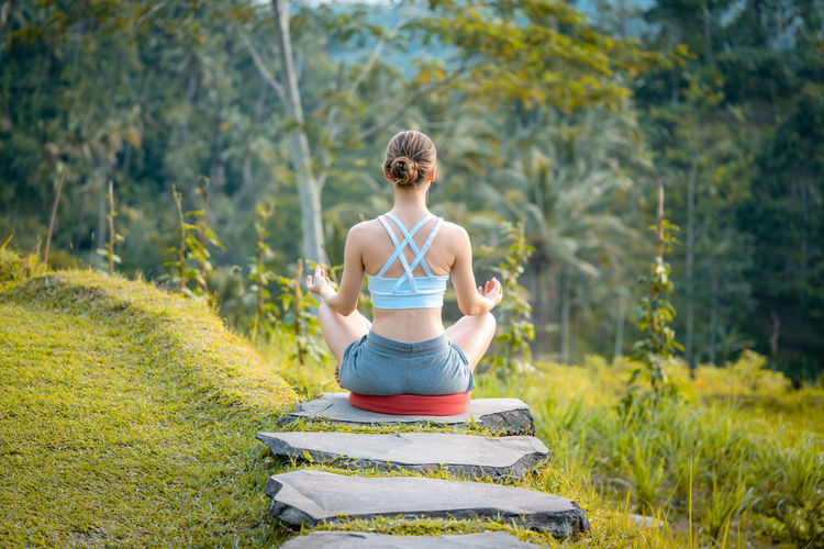 Young woman on path into the tropical jungle in yoga lotus pose doing relaxation exercises