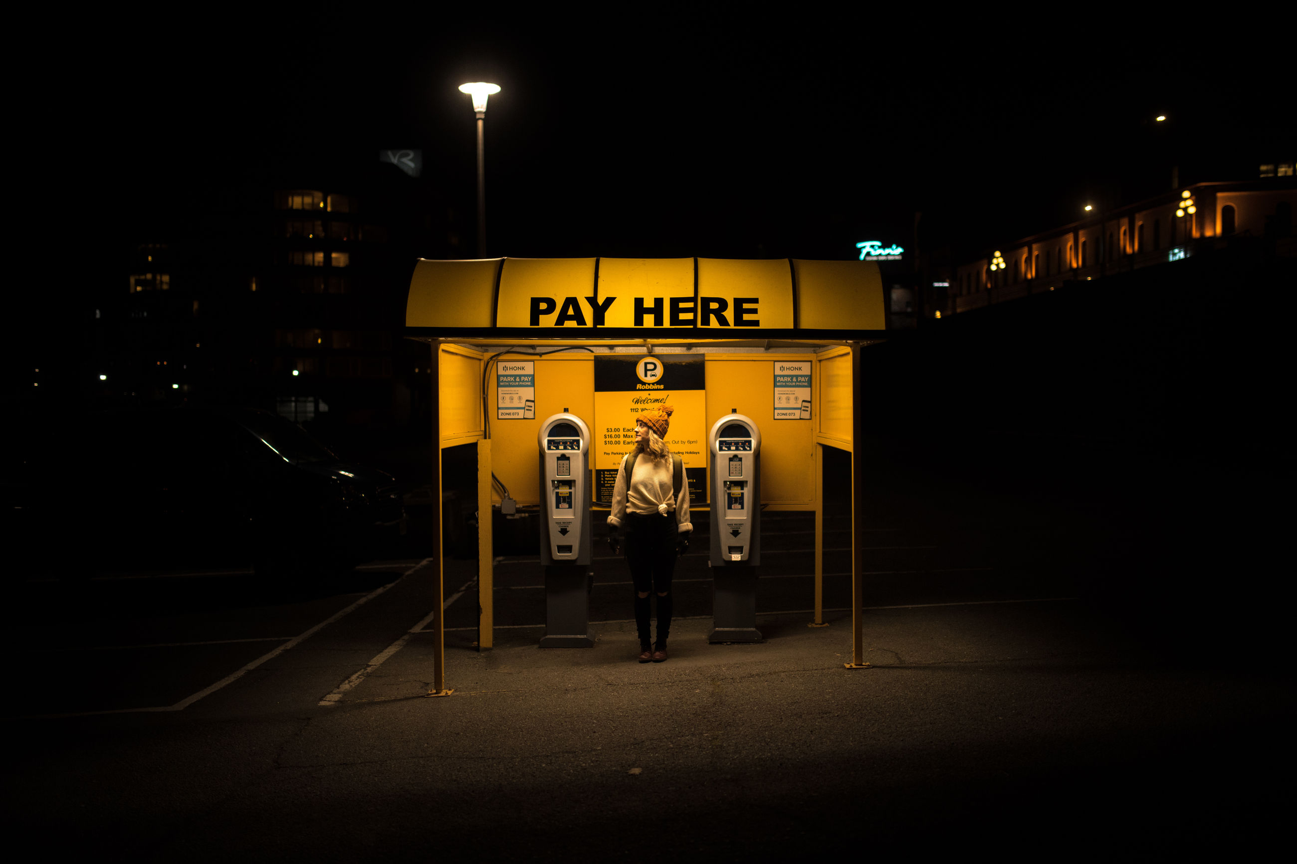 illuminated, night, architecture, text, built structure, building exterior, western script, communication, sign, city, real people, one person, full length, street, lifestyles, capital letter, lighting equipment, outdoors, footpath, transportation