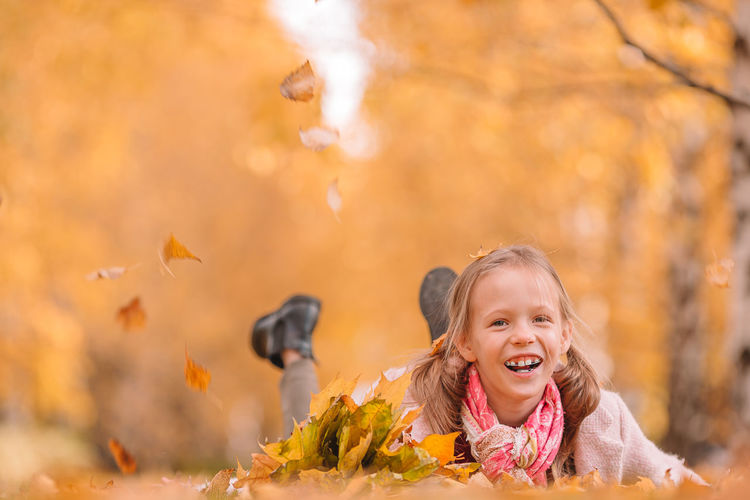 Portrait of smiling girl with leaves during autumn