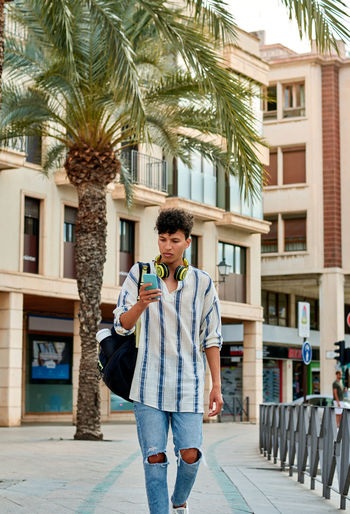 Full length of young man standing against palm trees