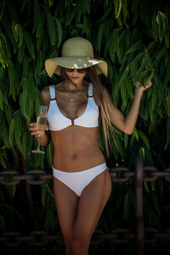 Woman in white bikini having champagne while standing against tree
