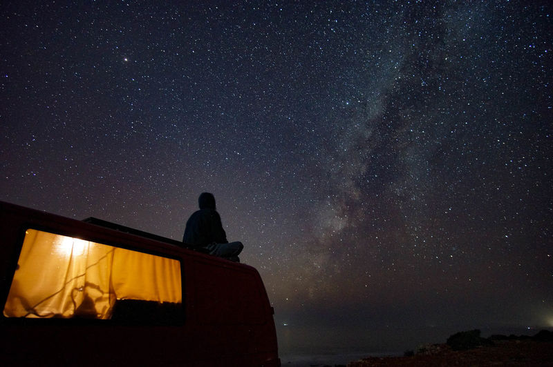 Woman sitting on motor home against sky at night