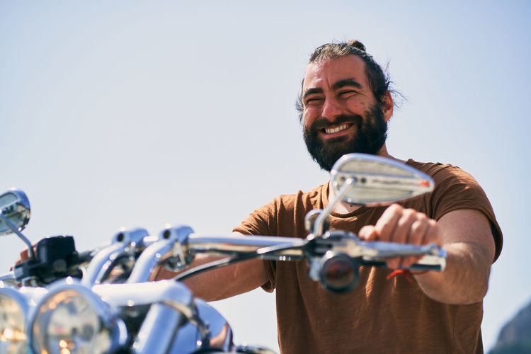 Man holding bicycle against clear sky