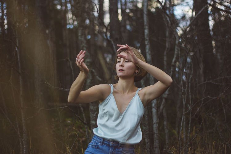 Young woman dancing against trees in forest