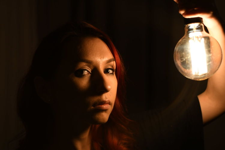 Close-up portrait of young woman holding light bulb on black background