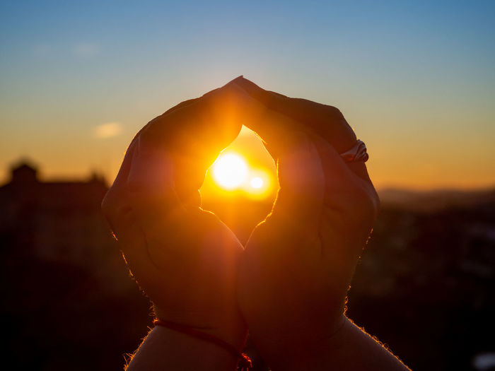 Close-up of woman holding sun during sunset