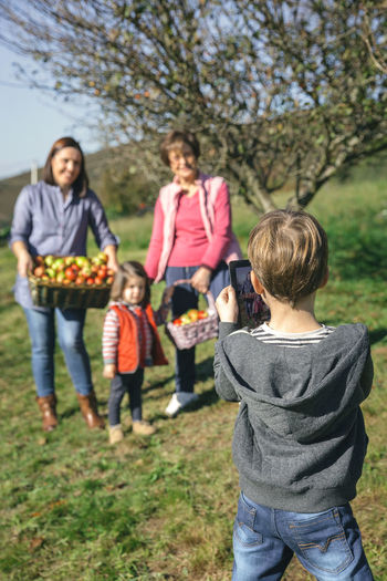 Rear View Of Boy Photographing Family From Digital Tablet On Field