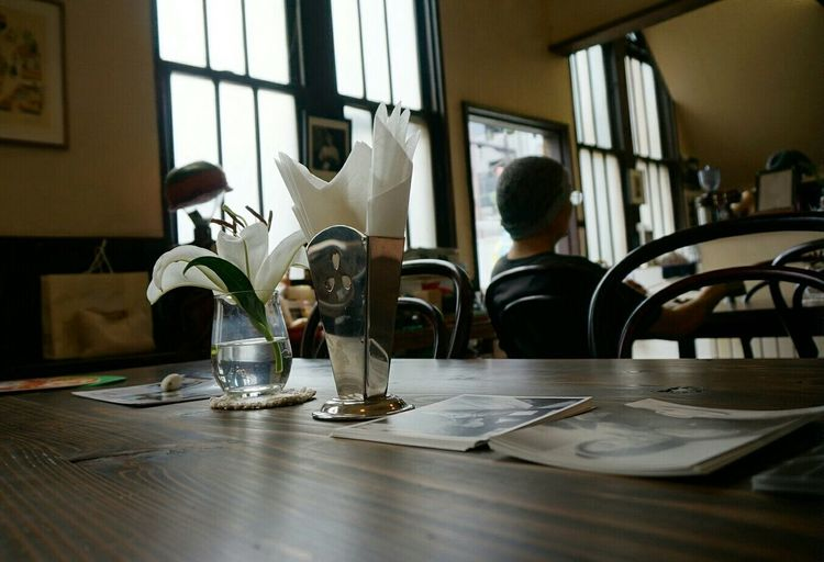 Flower Vase And Tissue Papers On Table At Coffee Shop