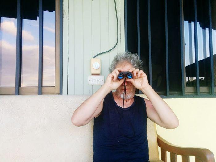 Mature man looking through binoculars