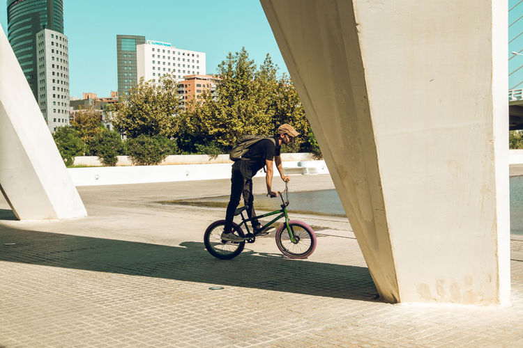 Side view of man riding bicycle against building
