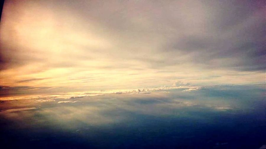 On an Airplane Early Flight to Punta Cana with a Sunlight sunrise in the Clouds.