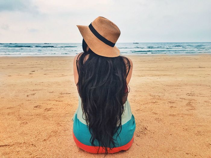 EyeEm Selects Sea Rear View Beach Real People Horizon Over Water Hat One Person Sand Leisure Activity Water Sky Shore Nature Scenics Lifestyles Beauty In Nature Sun Hat Tranquility Women