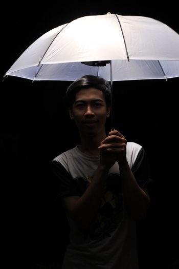 Man holding umbrella against black background