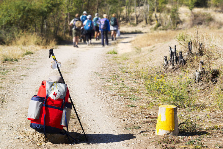 Close-Up Of Backpack And Hiking Pole With People In Background On Footpath