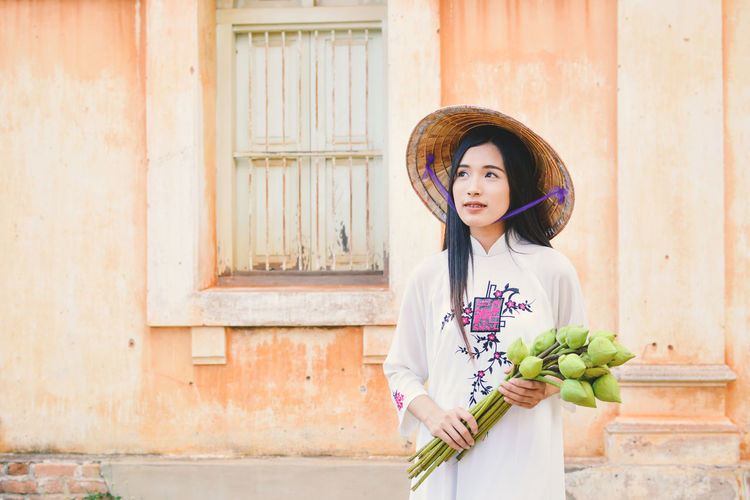 Portrait of young vietnamese woman standing against house