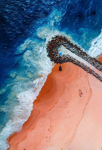 Aerial shot of waves and groin at city beach in perth. western australia