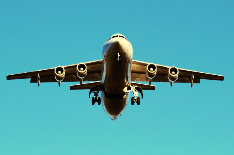 Low angle view of airplane in flight against clear blue sky