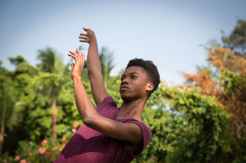 Low angle view of young man dancing against trees