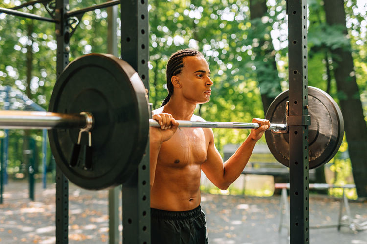 Shirtless man holding barbell while standing outdoors