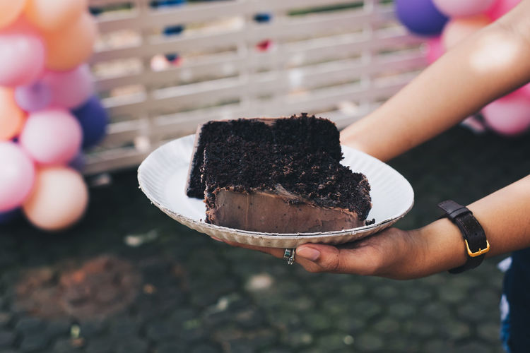 two slices of moist chocolate cake Human Hand Hand Human Body Part Food Holding Food And Drink One Person Real People Sweet Food Dessert Sweet Indulgence Freshness Unhealthy Eating Lifestyles Cake Temptation Chocolate Baked Body Part Sharing  Giving Party Backgrounds Sugar A New Perspective On Life Holiday Moments Moments Of Happiness