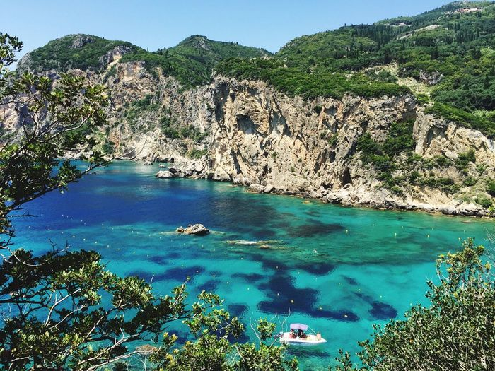 Deep blue waters of Palaiokastritsa Water Rock - Object Nature Beauty In Nature Scenics Mountain Rock Formation Sea Idyllic No People Cliff Beach Blue Tranquility Tranquil Scene Day Outdoors High Angle View Plant Tree