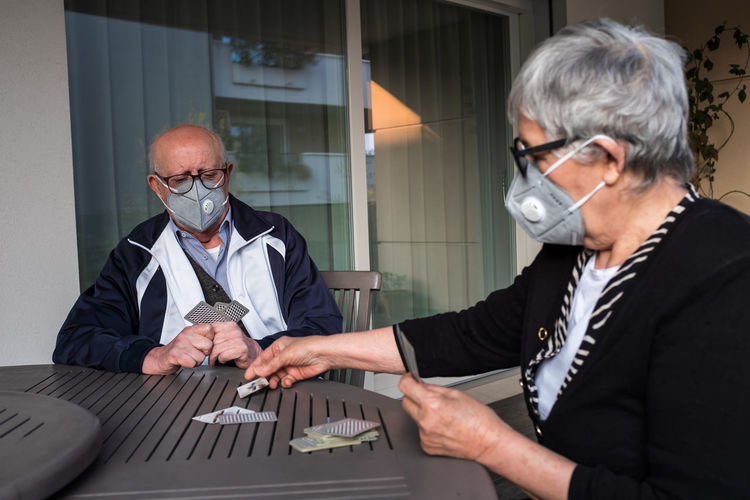 Italian's older people lockdown. a married couple play with game of the cards.