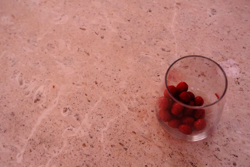 High angle view of red berries on glass