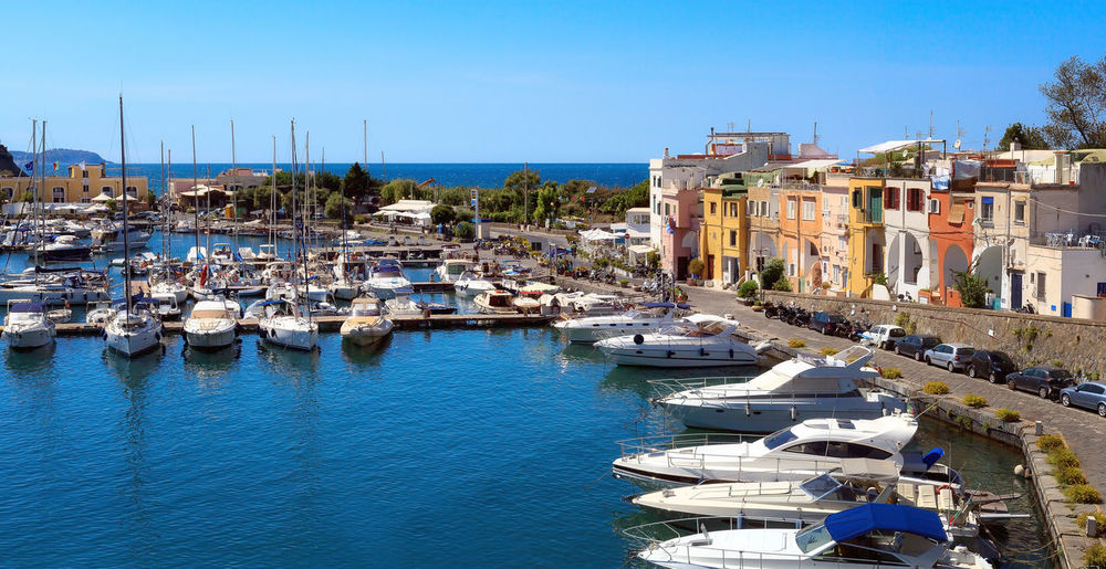Panoramic view of the small harbor of Chiaiolella Marina. On the right are the colorful houses of fishermen. Bay Area Architecture Blue Building Exterior Built Structure Chiaiolella Cityscape Clear Sky Day Harbor House Marina Moored Nature Nautical Vessel Outdoors Procida Sailboat Sea Sky Sunlight Town Travel Destinations Water Yacht