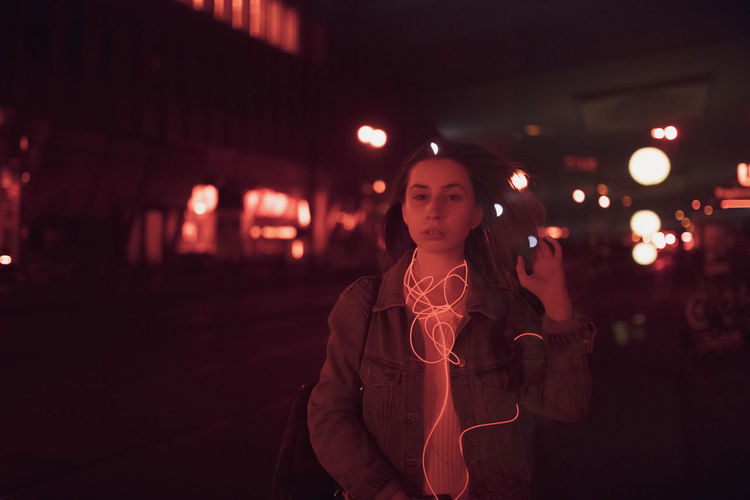 Portrait of young woman standing on road at night