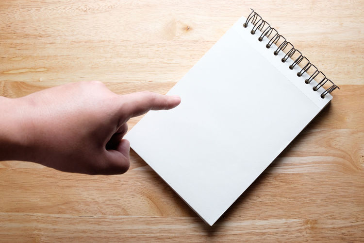 High angle view of person hand pointing over notepad on table