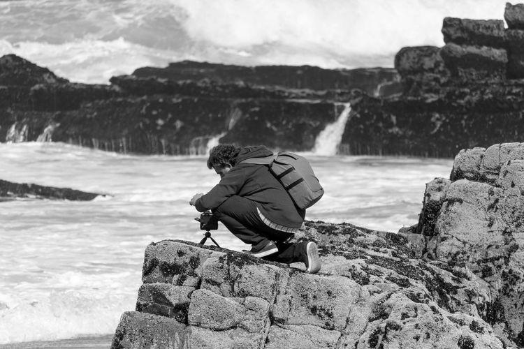 Rear view of man on rock at shore