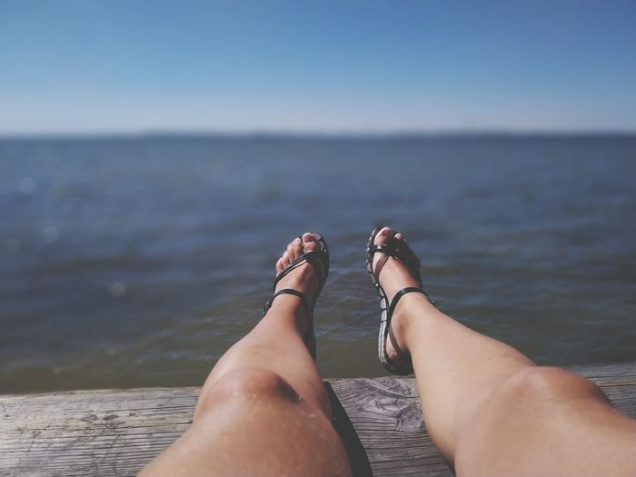 Low section of woman relaxing on pier over sea