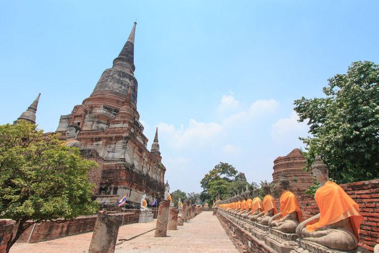 Buddha statues in row against sky at wat yai chai mongkhon