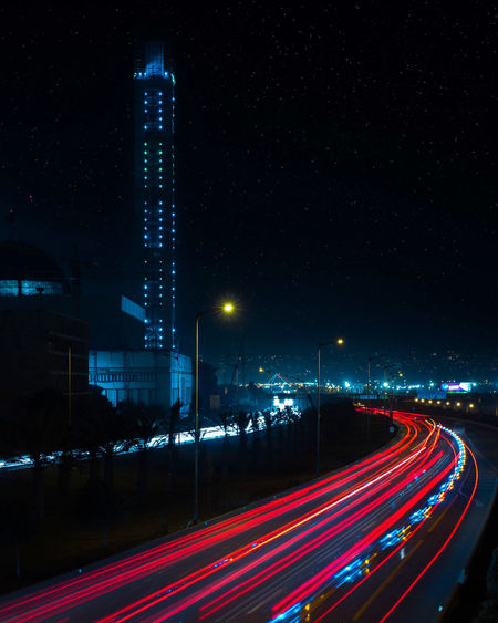Light trails on road against sky at night