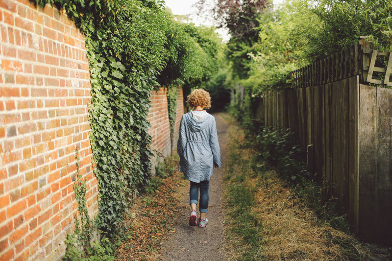 Blonde Brick Wall Built Structure Casual Clothing Curly Hair Day Epsom Epsom Downs Racecourse Footpath Full Length Girl Green Color Growth Leisure Activity Lifestyles Outdoors Person Standing Sunset Tree Wall - Building Feature Young Adult Summer Exploratorium