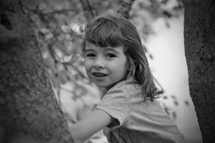 Close-up portrait of cute girl amidst trees