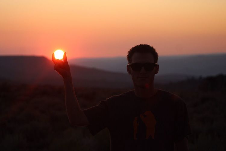 Optical illusion of silhouette man holding son at sunset