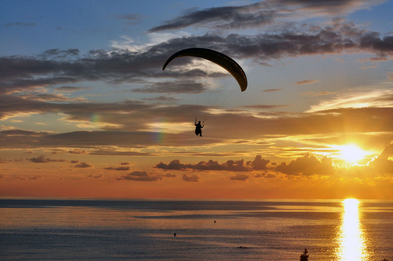 Silhouette Paragilider Over Sea Against Sky During Sunset