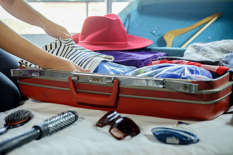 Cropped image of woman packing luggage on bed