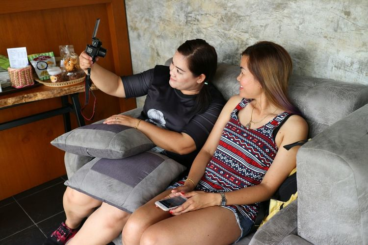 Woman with friend taking selfie through camera at home