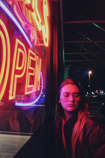 Young Woman By Illuminated Neon Lights At Night