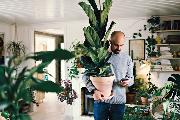 Full length of man standing in potted plant