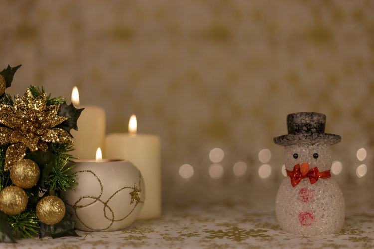 Close-Up Of Christmas Decorations With Candles On Table