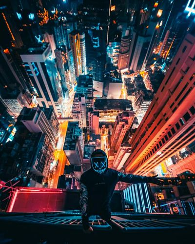 Portrait of man standing in illuminated city at night