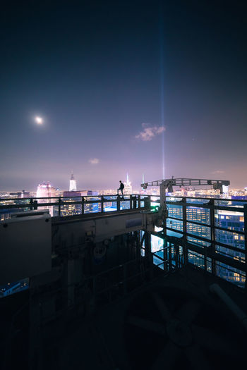 Illuminated pier by sea against sky in city at night