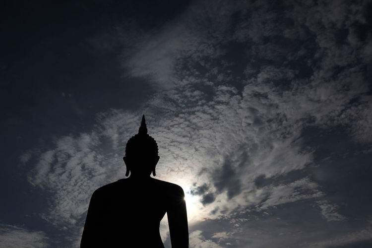 Low angle view of silhouette buddha statue against sky