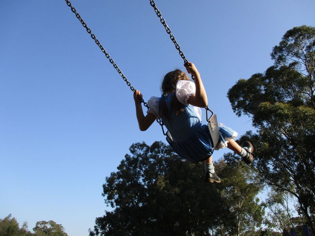 Blue Childhood Clear Sky Daredevil Day Dorothy Enjoyment Full Length Gingham Girls Happiness Leisure Activity Lifestyles Low Angle View Nature One Person Outdoors People Playground Real People Sky Swing Swings Tree Vichy