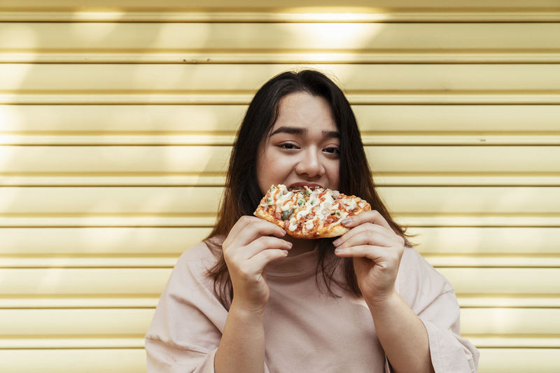Portrait of smiling young woman eating food against wall