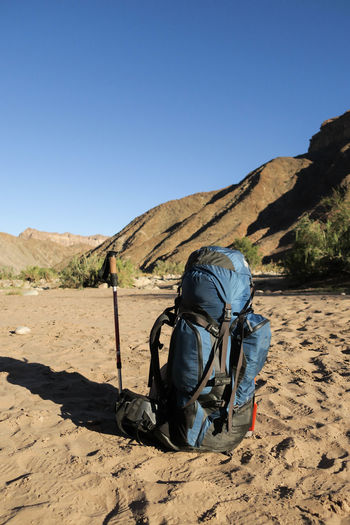 Hiker's backpack sitting on top of sand with walking stick alongside in scenic river valley Adventure Arid Climate Backpack Bag Beauty In Nature Camping Clear Sky Day Distance Hike Hiking Mountain Nature One Person Outdoors Packed Sand Sunlight Travel Walking Let's Go. Together.
